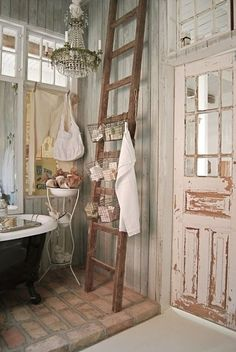 """I'm in love with the rustic, weathered look of this bathroom as well as the funky additions and added functionality with baskets and bowls. A  vintage chandelier and my dream claw-foot tub on apparent reclaimed bricks makes this a bathroom I could spend hours luxuriating in. Pour in the bubbles, grab your wine, and say """"ahhhh..."""""""