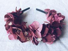 """La """"diadema MIDI magenta"""" es una diadema montada con flores preservadas. La base de esta diadema es de de hortensia de color granate y fucsia oscuro con detalles tostados y blancos. Es una diadema flexible que puede adaptarse a cualquier medida de cabeza. Puede llevarse tanto como diadema o sujeto encima de un recogido en la parte posterior. El packaging de la diadema es una caja de cartón que permitirá conservarla largo tiempo. Invitada perfecta. Wedding."""