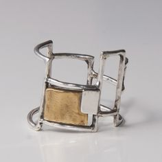 A sterling silver ring with a brass plate designed as a mondrian inspired grid.