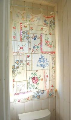 Vintage embroidered linens sewn together to make a curtain. Pieces of ribbon sewn at the top to attach it to the rod. by trina