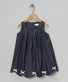Tiny pearls and bitty bows play with pleats on this darling denim dress. This sweet frock is easy to slip on thanks to its roomy swing cut and a zipper in back.