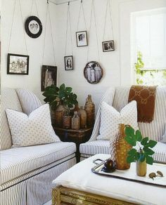 Loving the striped slipcovers but especially the way the photos have been hung, using the home's picture rail.