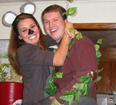 "This dual costume idea is the perfect excuse for you two to cuddle all night — since you're the koala climbing his tree! Wear a grey sweatshirt and dark skinnies. Smudge your nose with black makeup. Next, cut two ""ears"" out of a paper plate, color them grey and paste or tape them to a headband. For him, collect a bunch of fallen leaves and tape them to an earth-toned shirt (aka the trunk) so that he looks like a tall tree. 