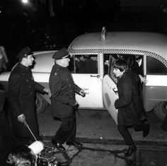 Police security is on hand for the arrival of The Beatles as guitarist George Harrison leads the way from a taxi-cab to Carnegie Hall's stagedoor on W. 56th St. in New York City on February 12, 1964.