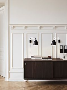 Warm white walls / cabinet / wall lights / herringbone wooden floors