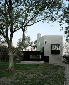 Board-marked concrete forms the walls of this rural home designed by Belgian studio Marie-José Van Hee Architecten