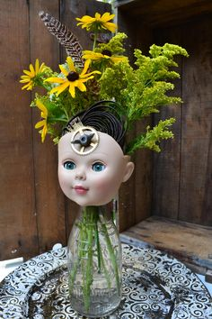 Repurposed doll head with clock parts and vintage bottle as vase