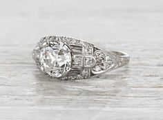 Vintage Edwardian engagement ring made in platinum and centered with a GIA certified 1.89 carat old European cut diamond with J color and VS2 clarity. Circa 1915. A beautiful ring featuring all the classic Edwardian motifs: open venting, feminine scrollwork, and intricate engravings. Diamond and gold mining has caused devastation in areas such as Africa, wreaking havoc on delicate ecosystems and communities. Choosing to go vintage, you are eliminating the need for more mining and lessening…