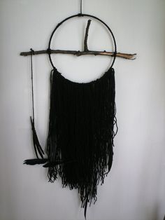 A homemade dream catcher/ wall hanging made from a tree twig, black wool and black feathers hanging from a 8 inch craft hoop. The piece is 36 inches