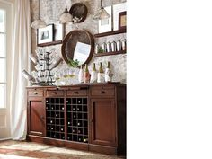 Prefect idea for a naked dining room wall. A lively, multi-level display makes this bar a festive focal point for holiday entertaining. The bar's open grid holds an ample wine collection, and on its broad top, five favorite vintages are wrapped in colorful bar towels. Wall-mounted shelves and baskets showcase objects like mementos, framed prints and a collection of cocktail shakers. Three mercury glass pendants illuminate the space, casting a warm bright glow.