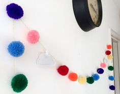A lovingly handmade garland with 21 wool pom poms in rainbow colours and two hand sewn felt clouds. The pom poms are approximately 4cm and the garland is 2m long. The pom poms are fixed on the twine at even spaces to keep them in place.  This would look great in a nursery, living room, bedroom, hanging outdoors or anywhere else you fancy and makes an ideal reusable decoration for parties and events. The garland ends with a pom pom so it can easily be hooked over a pin or nail or wrapped…