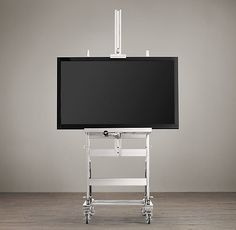 Gunmetal TV Easel - gives televisions, mirrors and other wall décor a home worthy of a gallery setting. Placed on casters and fashioned from an adjustable base of metal and wood, this sturdy easel can be positioned precisely as desired.