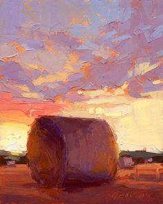 Landschap met hooibaal en op de achtergrond een ondergaande zon die voor mooie kleuren zorgt