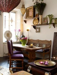 Bohemian dining area. Gold lamp, candlelight, greenery. Ethnic decor.