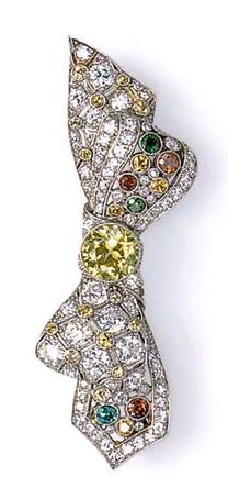 A COLORED DIAMOND BOW BROOCH  Designed as a pierced bow, set with old European and single-cut diamonds and circular multi-colored diamonds, bezel-set with a circular-cut yellow diamond knot, mounted in platinum The colored diamonds have not been tested for natural color