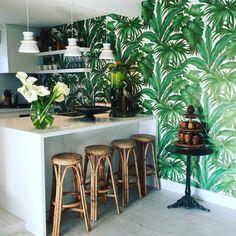 tendance tropicale dans la cuisine, cuisine ouverte équipée d'un îlot central, papier peint feuille de bananier