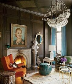 Great elements of decor - Love the old Victorian fireplace, the Chesterton sofa and the marble bust...striking portrait and the orange chair as pop of color and the whimsy of the ship chandelier