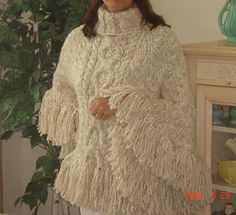 Knit back and forth with large cable pattern on the front and fringe trim. Also called fringed poncho.