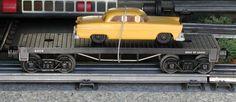 Lionel postwar # 6404 flatcar with a yellow automobile.