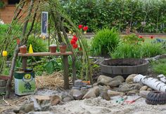 Garten mit einer Sandgrube und einem Blumenbeet im Hintergrund.