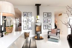 Aaaammmmazing idea for extension...Black and white wall decor with elements of pink and grey  Freestanding fireplace on beam wall... Armchair by fireplace facing dining table and kitchen...  Seated area with chaise longer type seat as room separator... Large sofa on far wall and  big armchair...