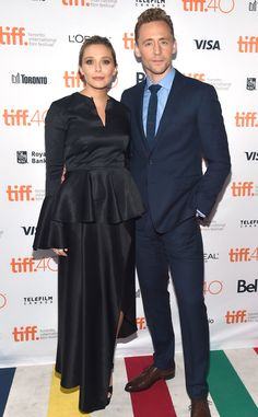 TIFF, Elizabeth Olsen, Tom Hiddleston. Unfortunate choice of dress for Lizzie. Nobody looks good in a peplum, and black shiny fabric does not photograph well.