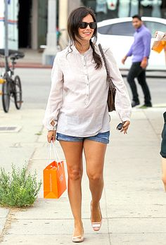 Mom-to-be Rachel Bilson swept her hair into a loose side braid and wore an ivory henley shirt with cuffed jean shorts while shopping in L.A. See all her best pregnancy looks!