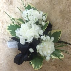 white mini carnations with baby's breath and black ribbon corsage