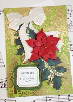 """Handmade Christmas Card. This lovely handmade Christmas card features a three dimensional paper poinsettia and a paper bow with elegant gold foil accents. These embellishments are layered on top of a beautiful gold foil patterned paper. """"Merry Christmas"""" in on the front of the card and the inside of the card has a sweet Christmas greeting: """"May Your Christmas be Wrapped in Happiness and Tied with Love."""""""