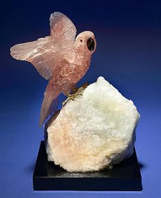 <i></i><i>By Peter Mueller<br />Brazil</i> <br />Fine, translucent Brazilian rose quartz has been used in this realistic carving of a parrot with with outstretched wings.  The beak is carved of rubellite tourmaline, the eyes are formed of cabochon garnets, the gold vermeil feet rest upon a boulder of massive two-color beryl--morganite to one side and pastel green beryl to the other. Raised on a black acrylic base. <i>Height 14in</i> <br /> <i></i>