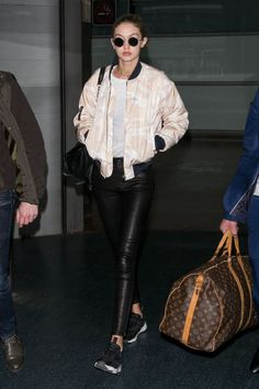 In tight leather leggings and a Ganni pastel bomber jacket at Aeroport Roissy in Paris, France.