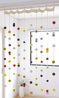 hanging pom poms threaded on yarn Closet, anybody?