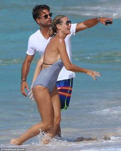 Beach babe: Flaunting her long legs and slim physique, the halterneck one-piece showcased her figure to perfection