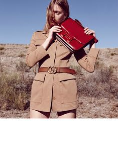 Tess poses in a brown jacket featuring a Gucci belt and oversized red Hermes clutch for Marie Claire Italia Magazine May 2016 issue