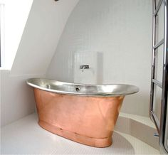 A freestanding copper tub makes a stunning centerpiece in a bathroom. Copper is naturally resistant to mold and bacteria which makes it low maintenance and easy to clean. Copper Tub, Copper Bathroom, Concrete Interiors, Neutral Color Scheme, Contemporary, Modern, Stainless Steel, Interior Design, Centerpiece