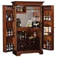 This Hide-A-Bar cabinet features paneled doors with inset panels of Ash Burl veneers in a parquet pattern framed with decorative moldings and oversized antique brass finished door knobs. Stores up to 22 bottles of wine, with a generous amount of room in the doors for liquor storage. An upper fixed shelf may hold glasses and tumblers. The cabinet is finished in Hampton Cherry with light distressing on select hardwoods and veneers.  Wooden stemware racks. Front locking doors. The left door is…