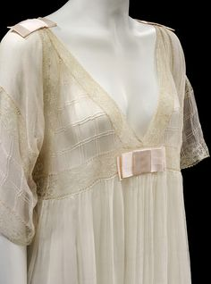 Nightdress, 1913. Fine, sheer pink silk georgette and white chiffon nightgown, short squared off sleeves and Empire line V-necked bodice, no shaping, trimmed with machine-made ecru lace insertion and flat pink satin ribbon bows. Voluminious white chiffon skirt.