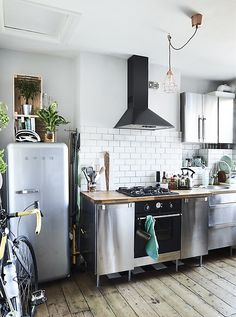 A stainless-steel kitchen with wooden floor.