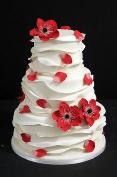 Scattered petals and red fondant anemones add color to a ruffled white cake.