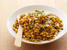 Bobby grills corn in its own husks to protect it before taking the smoky kernels off the cob and tossing them with Cotija cheese, lime juice, lime zest, ancho chile powder and creme fraiche.