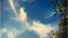 A strip of cloud with a rainbow entwined.