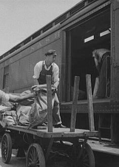 Men load mail into the storage section of a 30-foot Railway Post Office car at a station along the Louisville and Nashville Railroad in northern Florida in June 1940. This photograph was taken by Photographer Marion Post Wolcott during the 3 ½ years she spent documenting rural America for the U.S. Farm Security Administration.