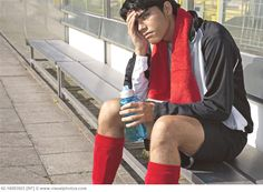 Soccer Player Sitting Alone on Bench After Losing Game