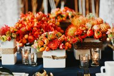 If you use navy table cloths, it's good to keep the flower & vase colour simple like this orange & white idea.