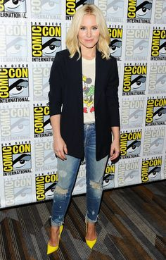 Kristen Bell in a Mickey Mouse T-shirt, black blazer, ripped jeans and yellow heels