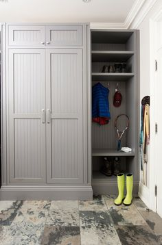 Gorgeous mud room with striking slate tiled floors beside floor to ceiling gray beadboard closets flanking mud room locker with bench and overhead cubbies above nickel coat hooks.