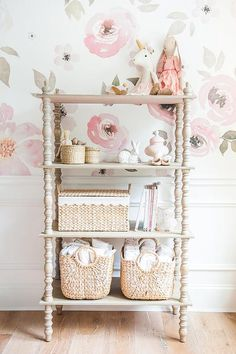A gorgeous gray Lyndsay Etagere, fitted with various woven storage baskets , sits in front of wainscotted lower walls in Behr Ultra Pure White accenting upper walls adoring pink floral Jolie wallpaper.