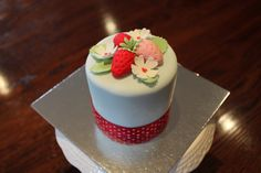 Mini cake with fondant strawberries and flowers.