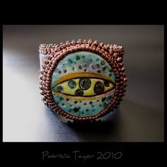 Cosmic Eye by Patrizia Tager - The following information was copied from Triz Designs etsy listing for this cuff: This beautiful, unique cuff was created around one of LisaPetersArts (www.LisaPetersArt.etsy.com) gorgeous OOAK round raku ceramic cabochon and is bead-embroidered using dark bronze Japanese seed beads. This centrepiece is attached to the chocolate brown genuine leather-covered brass cuff which is trimmed and embellished with the Japanese seed beads. The inside of the cuff is…