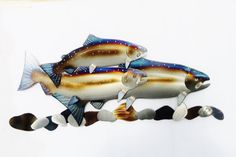 Three Rainbow Trout swimming above a multi colored River Rock bed.100% hand Made of 16 Ga. Steel. I hand draw and cut each piece. I then Grind the